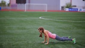 Piękna mięśniowa dziewczyna w rajstopy i kamizelce robi rozgrzewce przy stadium Krzyża napad, sprawność fizyczna, zdrowy styl życ zbiory wideo