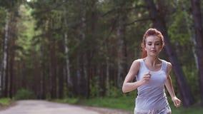 Piękna miedzianowłosa dziewczyna Jogging w lasowej atrakcyjnej dziewczynie bawi się plenerowego swobodny ruch zbiory wideo