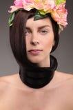 Piękna miedzianowłosa dziewczyna w kwiatach na szarym tle obraz stock