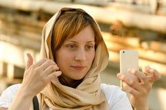 Piękna miedzianowłosa dziewczyna w szalika spojrzeniach w smartphone zdjęcia stock