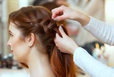 Piękna, miedzianowłosa dziewczyna z długie włosy, fryzjer wyplata Francuskiego warkocz w piękno salonie, zdjęcie stock