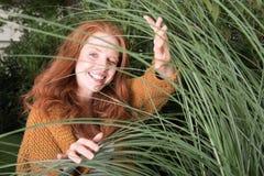 Piękna miedzianowłosa kobieta mruga przez traw Zdjęcia Royalty Free