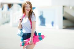 Piękna miedzianowłosa kobieta pozuje z deskorolka Zdjęcie Royalty Free