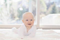 Piękna 6 miesięcy chłopiec Ubierająca w bielu & lying on the beach na Puszystej Białej Powszechnej Patrzeje kamerze Uśmiechnięty  obraz royalty free