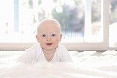 Piękna 6 miesięcy chłopiec Ubierająca w bielu & lying on the beach na Puszystej Białej Powszechnej Patrzeje kamerze Uśmiechnięty  obraz stock