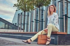 Piękna modna kobieta w elegancki odzieżowym i szkła z torebką, siedzi na ławce przeciw drapaczowi chmur zdjęcie stock
