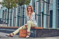 Piękna modna kobieta w elegancki odzieżowym i szkła z torebką, siedzi na ławce przeciw drapaczowi chmur obraz royalty free