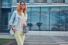 Piękna modna kobieta w elegancki odzieżowym i szkła z torebką, stoi przeciw drapaczowi chmur obrazy royalty free