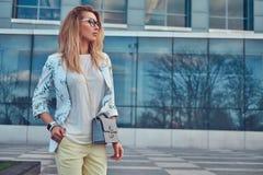Piękna modna kobieta w elegancki odzieżowym i szkła z torebką, stoi przeciw drapaczowi chmur fotografia royalty free