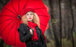 Piękna modna młoda dziewczyna z czerwonym parasolem, czerwoną nakrętką i czerwień szalikiem w parku, Fotografia Stock