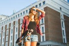 Piękna modniś dziewczyna z łyżwa deskowymi jest ubranym okularami przeciwsłonecznymi obrazy royalty free