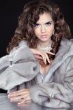 Piękna mody brunetki dziewczyna w wyderkowym futerkowym żakiecie odizolowywającym na bla Zdjęcia Royalty Free