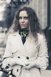 Piękna mody kobieta w białym okopu żakieta odprowadzeniu w miasto ulicie Fotografia Stock