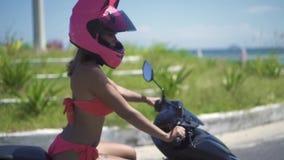 Piękna moto kobieta w różowym bikini i hełma jeżdżeniu na motocyklu na morze plaży kształtuje teren zwolnione tempo piękna kobiet zdjęcie wideo