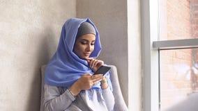 Piękna Muzułmańska dziewczyna Używa Smartphone w kawiarni Nowożytna Muzułmańska kobieta i nowe technologie Obrazy Royalty Free