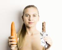 Piękna naga młoda kobieta je marchewki marchewka vs czekolada zdrowy jedzenie - silny zębu pojęcie Zdjęcie Royalty Free