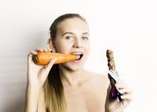 Piękna naga młoda kobieta je marchewki marchewka vs czekolada zdrowy jedzenie - silny zębu pojęcie Zdjęcia Royalty Free