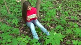 Piękna nastolatek dziewczyna z pastylka komputerem siedzi na trawie w parku Film statyczna kamera zbiory
