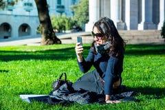 Piękna nastoletnia dziewczyna patrzeje jej smartphone z ciemnym włosy i słońc szkłami fotografia royalty free