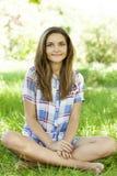 Piękna nastoletnia dziewczyna w parku przy zieloną trawą. Zdjęcia Stock
