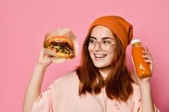 Piękna nastoletnia dziewczyna z czerwonym mienie hamburgerem, napojem w oba rękach włosy i kapeluszu i zdjęcia stock