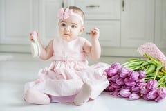 Piękna niemowlak grępla trzyma włosy w ładnych sukniach przeciw jako tła popasu pojęcia dolarom szarość wiesza haczyka Fotografia Stock