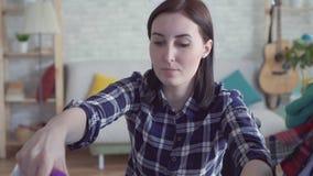 Piękna niepełnosprawna kobieta w wózku inwalidzkim robi pracie domowej, Odprasowywa odziewa zbiory wideo