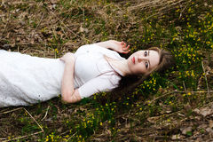 Piękna niewinnie kobieta w biel sukni lying on the beach na trawie Zdjęcie Royalty Free