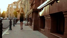 Piękna nikła młoda blondynka iść dalej w czarnej sukni zbiory wideo