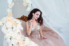 piękna odosobniony portreta biel Piękna kobieta siedzi wśród białych kwiatów z zmysłowymi wargami Kosmetyki, makijaż mydlarnia Fotografia Stock