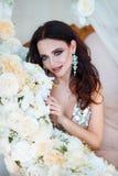 piękna odosobniony portreta biel Piękna kobieta siedzi wśród białych kwiatów z zmysłowymi wargami Kosmetyki, makijaż mydlarnia Zdjęcie Stock