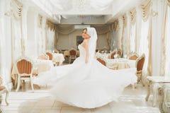Piękna panna młoda jest ubranym mody ślubną suknię z piórkami z luksusowym zachwyta makijażem i fryzurą, studio salowy obrazy royalty free