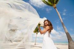 Piękna panna młoda pozuje przy tropikalną plażą Fotografia Royalty Free