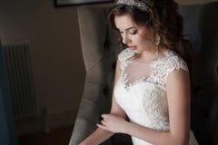 Piękna panna młoda w ślubnej sukni obsiadaniu w krześle w pokoju hotelowym Obrazy Royalty Free