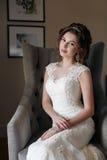 Piękna panna młoda w ślubnej sukni obsiadaniu w krześle w pokoju hotelowym Zdjęcie Stock