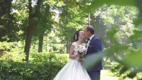 Piękna panna młoda w białej ślubnej sukni całuje z fornalem w kostiumu outdoors w parku w lecie zbiory