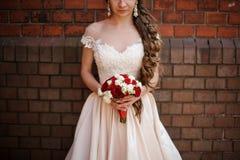 Piękna panna młoda w białej ślubnej sukni z bukietem czerwone i białe róże zdjęcia royalty free
