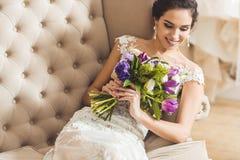 Piękna panna młoda z kwiecistym bukietem na kanapie fotografia stock