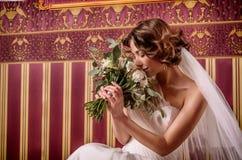 Piękna panna młoda z wspaniałymi spływanie kędziorami wącha flowersÑŽ fotografia stock