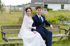 Piękna para małżeńska w ślubnych sukniach, pozuje dla fotografii strzelaniny w belarusian wiosce Zielony tło Fotografia Stock
