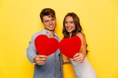 Piękna para pozuje przy kamerą, trzyma czerwonych serca Obrazy Royalty Free