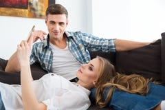 Piękna para relaksuje na kanapie i używa telefon komórkowego Obraz Royalty Free