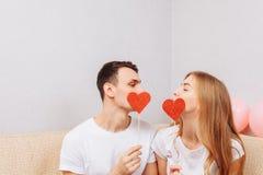 Piękna para w miłości, mężczyźnie i kobiecie w białych koszulkach, trzymający papierowych serca, siedzi na kanapie w domu zdjęcia royalty free