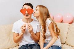 Piękna para w miłości, mężczyźnie i kobiecie w białych koszulkach, trzymający papierowych serca, siedzi na kanapie w domu obrazy royalty free