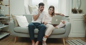 Piękna para w ranku rozkazie coś na telefonie od notatnika one siedzi w nowożytnej kanapie i zbiory wideo