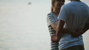 Piękna pary pozycja na brzeg opowiadać i jezioro Potomstwa dobierają się przytulenie na plaży na zmierzchu w wieczór zbiory