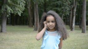 Piękna pięcioletnia stara mała afrykańska dziewczyna opowiada na telefonie komórkowym na pięknym letnim dniu w miasto parku zbiory wideo