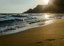 Piękna piaskowata Śródziemnomorska plaża przy zmierzchem i odciskami stopy na piasku Obrazy Royalty Free