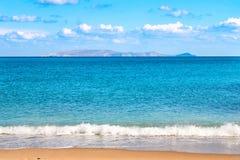 Piękna piaskowata plaża i miękki błękitny morze machamy na tle Dia wyspa, niebieskie niebo i obrazy royalty free