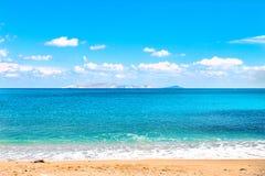 Piękna piaskowata plaża i miękki błękitny morze machamy na tle Dia wyspa, niebieskie niebo i kosmos kopii obraz stock